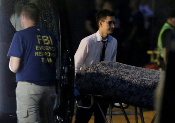 Police forensic investigators work at the crime scene of a mass shooting, as bodies are removed at the Pulse gay night club in Orlando, Florida, U.S. June 12, 2016. REUTERS/Jim Young