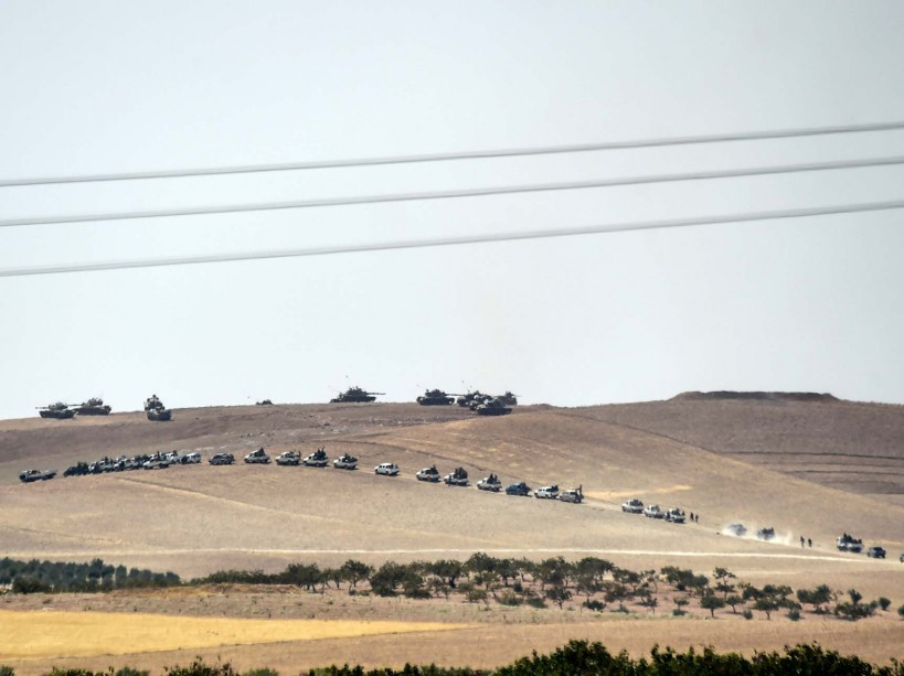 This picture taken from the Turkish Syrian border city of Karkamis in the southern region of Gaziantep, on August 24, 2016 shows Turkish army tanks and pro-Ankara Syrian opposition fighters moving two kilometres west from the Syrian Turkish border town of Jarabulus. Turkey's army backed by international coalition air strikes launched an operation involving fighter jets and elite ground troops to drive Islamic State jihadists out of a key Syrian border town. Turkey's state-run Anadolu news agency reported that pro-Ankara Free Syrian Army (FSA) rebels had already penetrated three kilometres (two miles) inside Syria towards the IS-held town of Jarabulus. The air and ground operation, the most ambitious launched by Turkey in the Syria conflict, is aimed at clearing jihadists from the town of Jarabulus, which lies directly opposite the Turkish town of Karkamis. / AFP PHOTO / BULENT KILIC