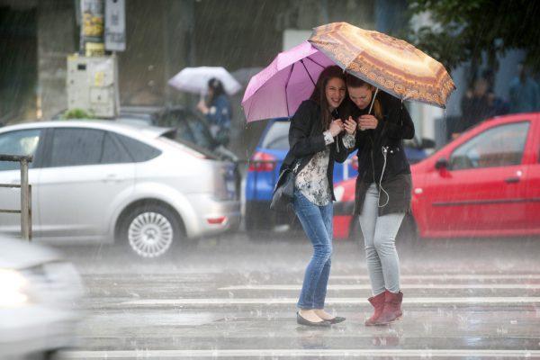 Doua tinere se adapostesc sub umbrele in timp ce asteapta sa traverse Soseaua Mihai Bravu in timpul unei ploi torentiale de vara, in Bucuresti, vineri, 20 iunie 2014. CODRIN PRISECARU / MEDIAFAX FOTO