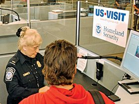 Homeland Security Secretary Tom Ridge, (L) watches Customs and Border Protection officer Mary Armbrust(C) use the new US-VISIT biometric program at Hartsfield-Jackson International Airport in Atlanta, Georgia, 05 January 2004. The system fingerprints and photographs visitors to the United States who require visas. Erik S. Lesser/Getty Images/AFP PHOTO / FOR NEWSPAPER AND TV USE ONLY
