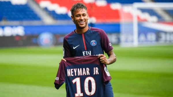 """Brazilian superstar Neymar poses with his new jersey during his official presentation at the Parc des Princes stadium on August 4, 2017 in Paris after agreeing a five-year contract following his world record 222 million euro ($260 million) transfer from Barcelona to Paris Saint Germain's (PSG). Paris Saint-Germain have signed Brazilian forward Neymar from Barcelona for a world-record transfer fee of 222 million euros (around $264 million), more than doubling the previous record. Neymar said he came to Paris Saint-Germain for a """"bigger challenge"""" in his first public comments since arriving in the French capital. / AFP PHOTO / Lionel BONAVENTURE        (Photo credit should read LIONEL BONAVENTURE/AFP/Getty Images)"""