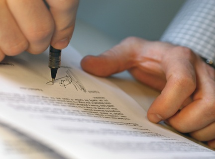 Man's Hands Signing Document --- Image by © Royalty-Free/Corbis